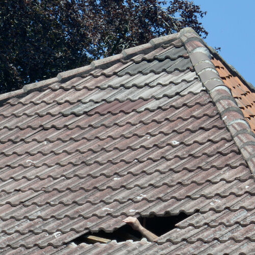 Damaged tile roof with a hole.