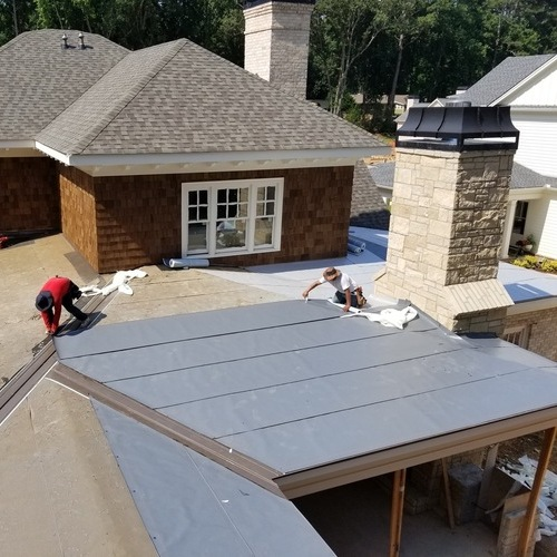 Workers installing a metal roof.