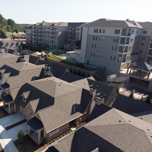 View from above of apartments with asphalt shingled roofs.
