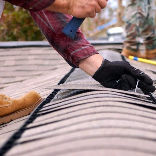 Close up of a worker repairing shingles